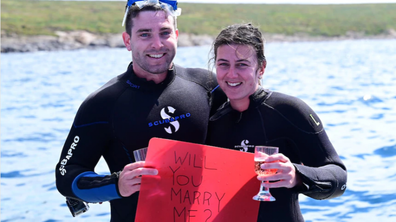 Hearts flutter during wedding proposal in shark cage